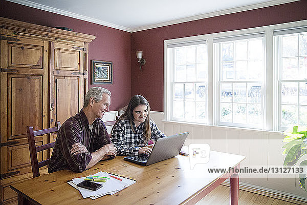Grandfather and granddaughter using laptop computer at table in home