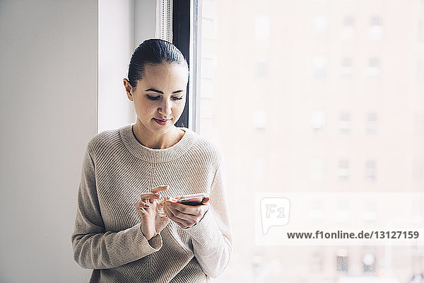 Woman using mobile phone while standing by window at home