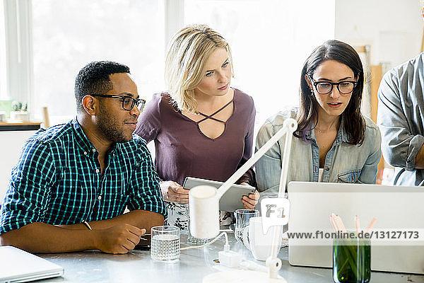 Geschäftsleute  die während einer Besprechung auf einen Laptop schauen