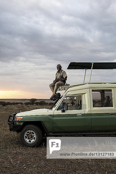Portrait of man sitting on off-road vehicle against cloudy sky at Serengeti National Park