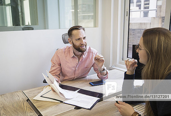 Kollegen diskutieren Berichte im Büro