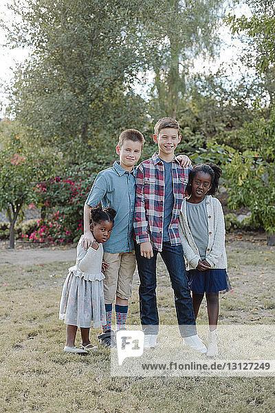 Portrait of siblings standing on field