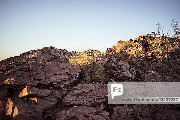 Low angle view of woman photographing while sitting on rock formations against clear sky