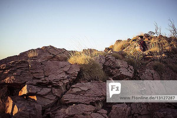 Tiefwinkelaufnahme einer Frau  die auf Felsformationen sitzend vor klarem Himmel fotografiert