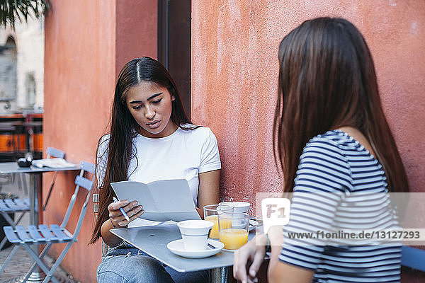 Woman reading documents while sitting with friend at sidewalk cafe