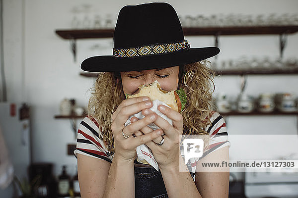 Close-up of woman wearing hat holding sandwich while standing at home