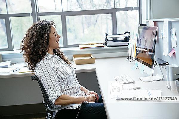 Seitenansicht einer lächelnden Geschäftsfrau,  die auf einen Desktop-Computer im Büro schaut