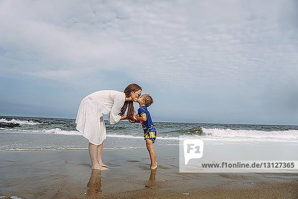 Mother and son kissing on mouth while standing on shore at beach against sky