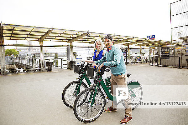 Portrait of happy mature couple standing with bicycles on footpath
