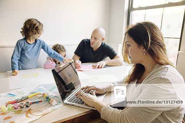 Woman using laptop computer while father assisting children in drawing at table