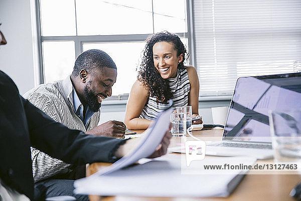 Fröhliche Geschäftsleute diskutieren bei Besprechung im Sitzungssaal