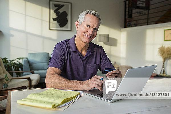 Porträt eines reifen Mannes  der einen Laptop-Computer benutzt  während er zu Hause Rechnungen bezahlt