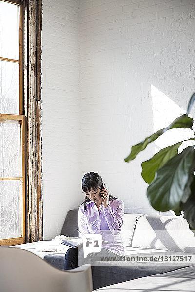 Geschäftsfrau schreibt in Buch  während sie im Kreativbüro mit dem Handy telefoniert