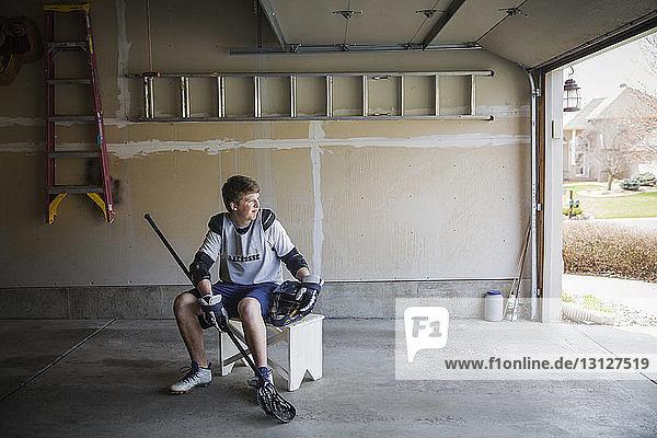 Junger Mann hält Lacrosse-Stick und sitzt auf einem Hocker