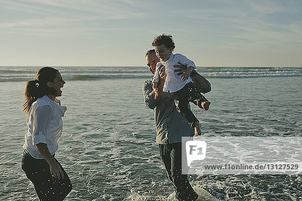 Happy mother looking at son carried by father on shore against sky