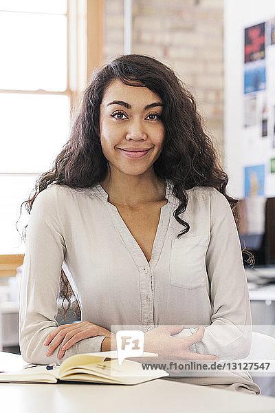 Porträt einer am Schreibtisch sitzenden Geschäftsfrau im Büro