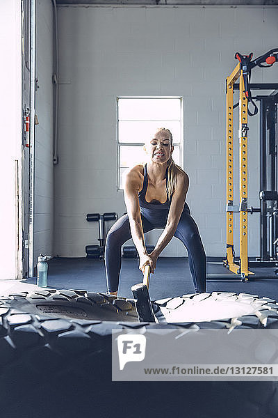 Determined woman hitting tire with sledgehammer while exercising in gym