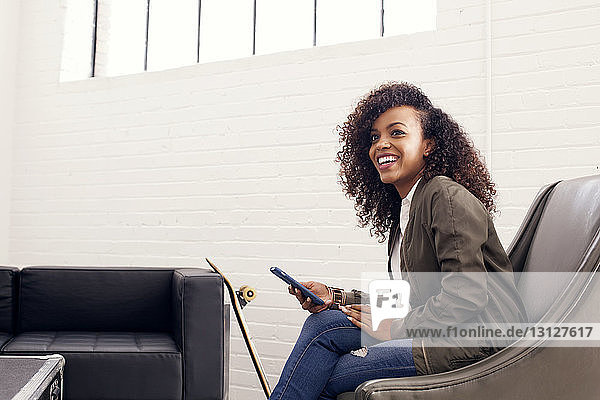 Confident businesswoman using phone while sitting on sofa at office