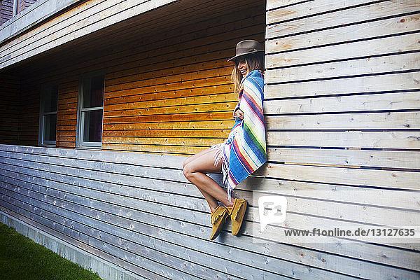 Fröhliche,  in eine Decke gehüllte Frau sitzt an den Fenstern eines Blockhauses
