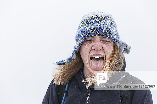 Close-up of playful woman wearing warm clothing sticking out tongue during winter