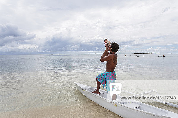 Side view of shirtless man blowing coach shell while standing in boat at beach against cloudy sky