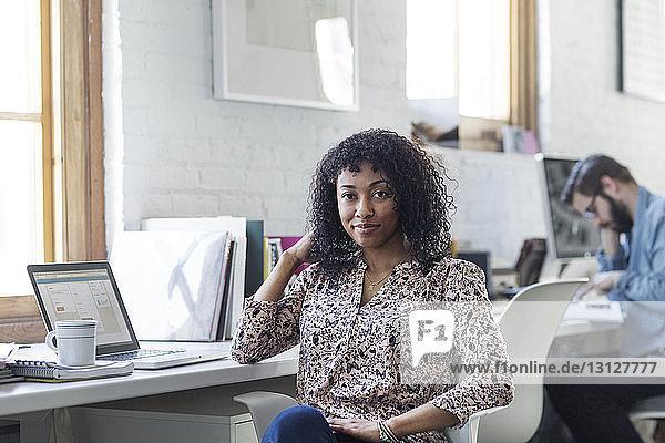 Porträt einer lächelnden Geschäftsfrau  die im Büro am Schreibtisch sitzt