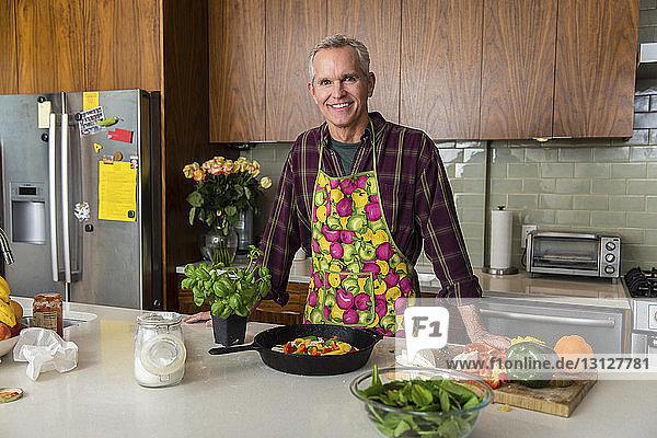 Porträt eines lächelnden reifen Mannes  der zu Hause in der Küche Pizza zubereitet