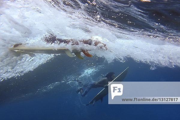 Friends surfing underwater in sea