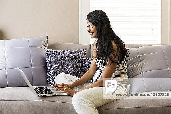 Glückliche schwangere Frau surft zu Hause mit dem Laptop im Internet