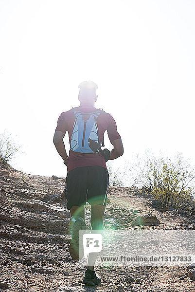 Rückansicht eines männlichen Wanderers mit Rucksack  der am sonnigen Tag auf dem Berg gegen den klaren Himmel läuft