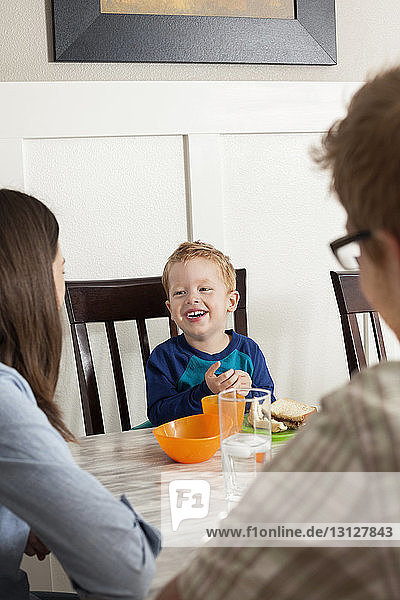 Parents sitting with boy having breakfast at home