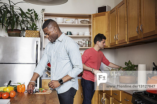 Homosexual males preparing food in kitchen