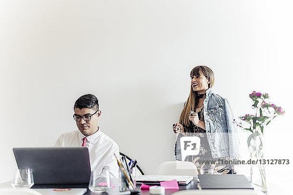 Geschäftsfrau steht an der Wand  während ein männlicher Kollege im Büro einen Laptop benutzt