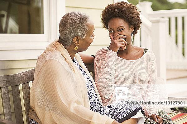 Ältere Frau sitzt mit Tochter auf der Bank im Innenhof