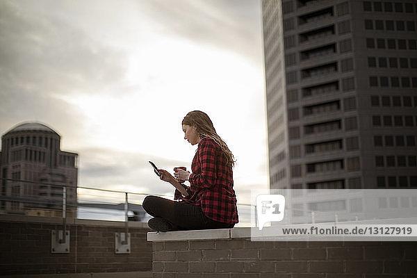 Frau benutzt Smartphone  während sie auf einem Sitzplatz auf einer Terrasse vor einem Gebäude sitzt