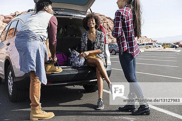 Freunde unterhalten sich am sonnigen Tag im Kofferraum auf dem Parkplatz