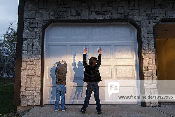 Playful brothers with arms raised standing in front of door during sunset