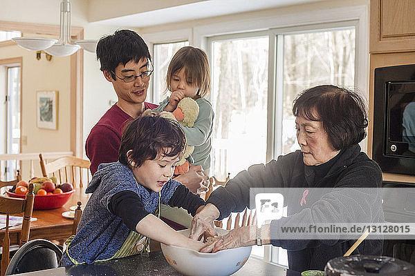 Vater trägt Tochter,  während er bei der Familie steht und zu Hause Essen zubereitet