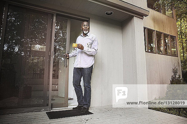 Senior man holding coffee cup while standing at entrance of house