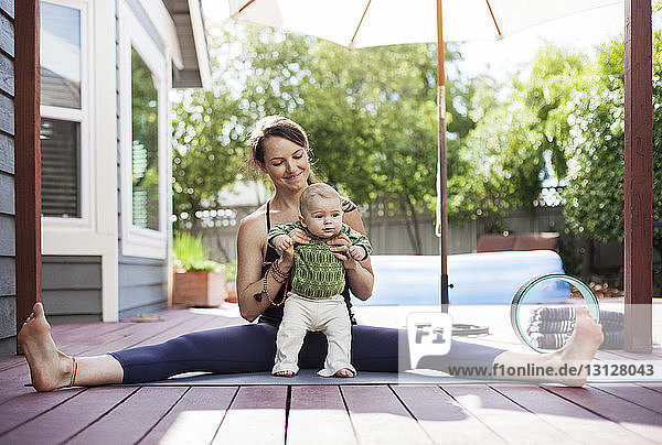 Happy mother holding baby while sitting with legs apart on mat