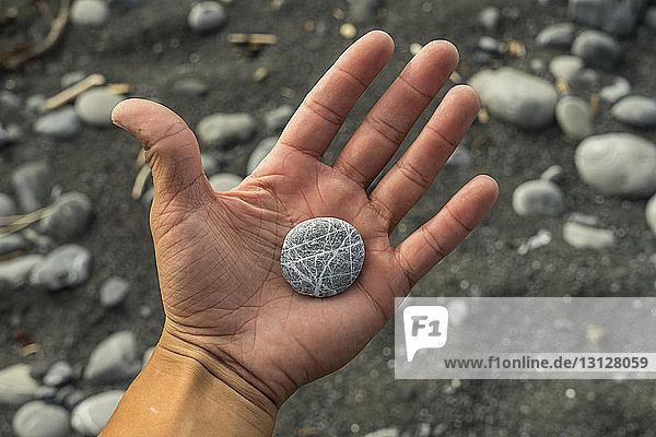 Abgetrennte Hand eines Mannes  der einen Kieselstein am Strand hält
