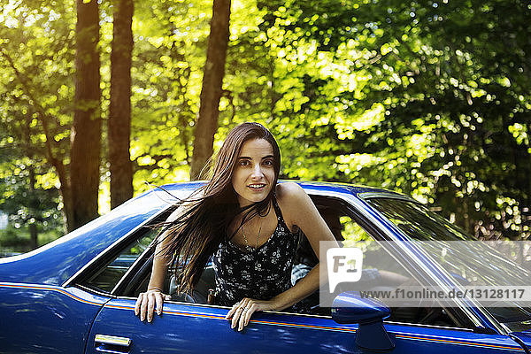 Portrait of woman leaning out of pick-up truck window in forest