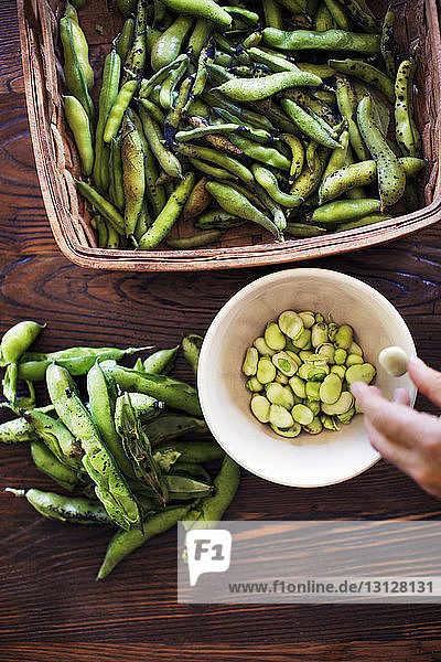 Cropped image of hand shucking beans at table