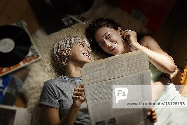 Draufsicht einer glücklichen Frau  die eine Vinyl-Schallplatte hält  während sie mit einem Freund auf dem Boden liegt