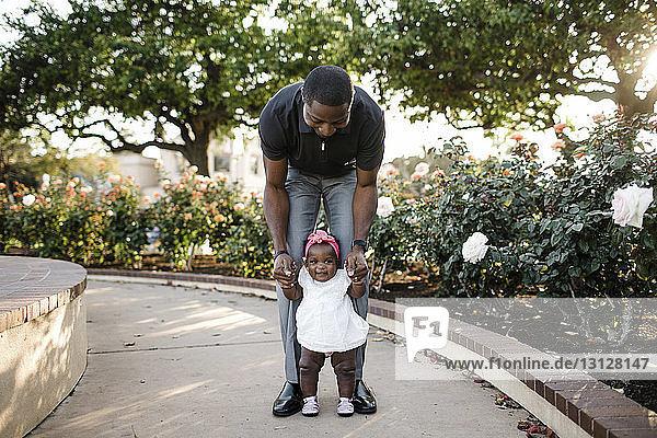 Vater hilft Tochter beim Stehen auf Fußweg im Park