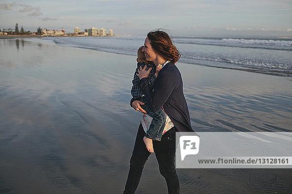 Seitenansicht einer Frau  die einen Jungen trägt  während sie am Strand spazieren geht