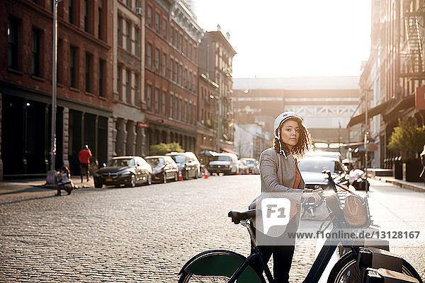 Geschäftsfrau hält Fahrrad auf Straßenparkplatz