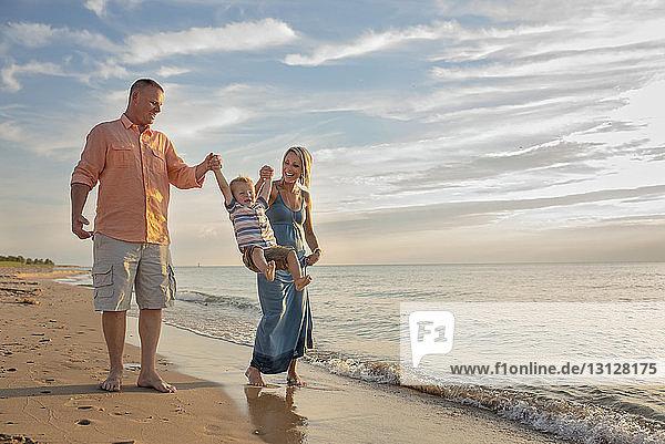 Verspielte Eltern halten die Hände ihres Sohnes  während sie ihn am Strand schaukeln