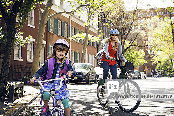 Portrait of happy mother and daughter riding bicycles on street