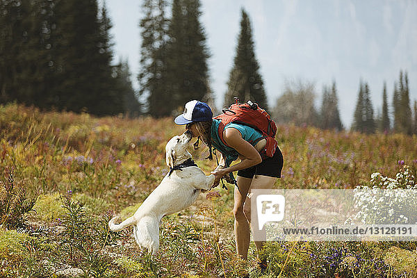 Woman with backpack kissing dog while standing on field
